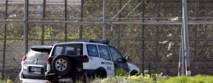 Varios coches de la Guardia Civil aparcados junto a la valla de Melilla. / FRANCISCO G. GUERRERO (EFE)