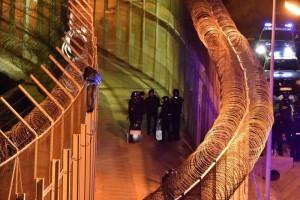 Un joven subsahariano permanece, ayer, encaramado a la valla fronteriza de Ceuta con Marruecos bajo la vigilancia de guardias civiles españoles. REUTERS