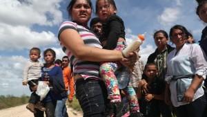 Inmigrantes centroamericanos con sus hijos esperan ser transportados por la policía de fronteras en Roma, Texas (John Moore / AFP)