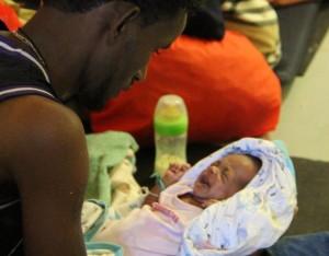 Un padre soltero coge a su bebé de una semana tras ser rescatados por Médicos Sin Fronteras en el Mediterráneo. | MSF