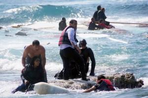 Un hombre rescata a una migrante en el este de la isla de Rodas, en mar Egeo, abril de 2015